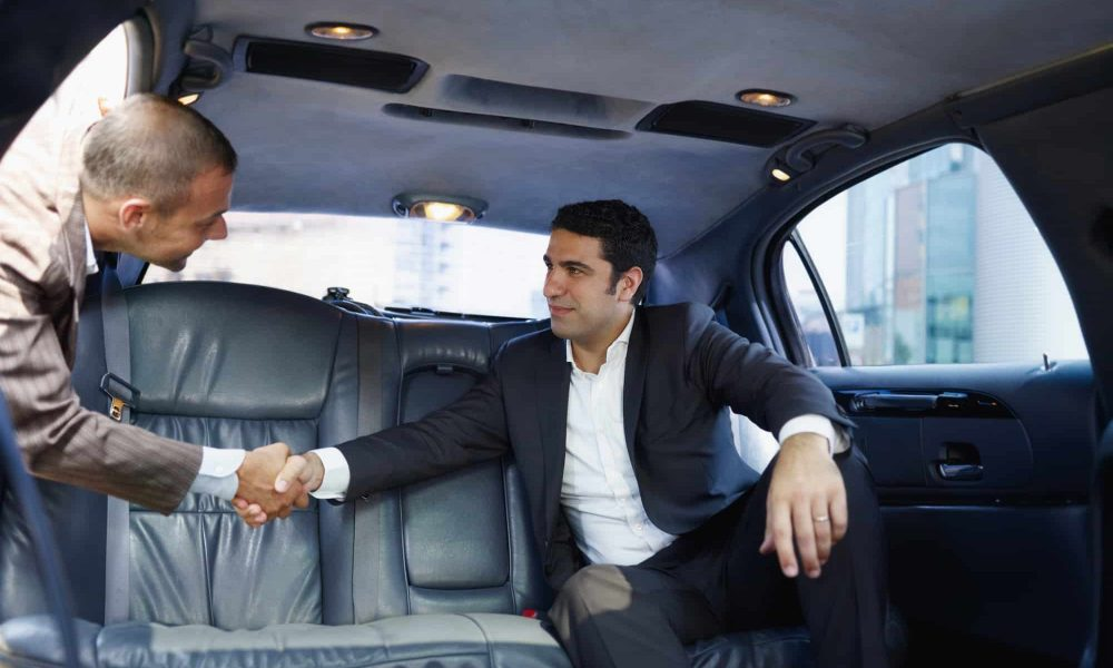 Two Male Entrepreneurs Meeting In Limousine For Business Travel And Shaking Hands. Front View, Low Angle Shot.